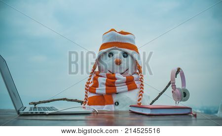 Snowman in winter with laptop headset and book. Xmas or christmas decoration audio book. New year snowman in hat. Happy holiday celebration new technology. Christmas and education fairytale.