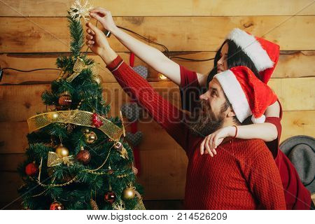 Couple in love in santa hat family. Winter holiday and celebration. Xmas party preparation. Christmas man and woman couple. New year guy and girl decorate Christmas tree.