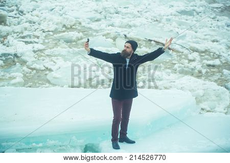 Winter holiday and new technology. man with frozen hummock and mobile phone. Cold weather and ice age. Cracked ice background and guy in Christmas. Man with beard make selfie photo at ice block.