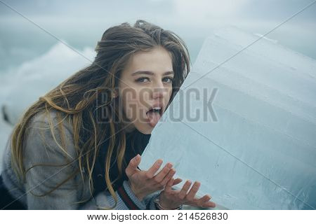 woman with pretty face lick ice block. girl with frozen hummock. Cold weather and ice age. Cracked ice background and woman in Christmas. Winter holiday and vacation.