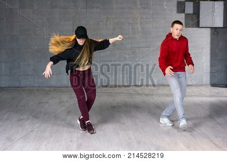 Couple of hip-hop dancers is dancing. Girl and boy performing street dance on studio background. School of modern dance.