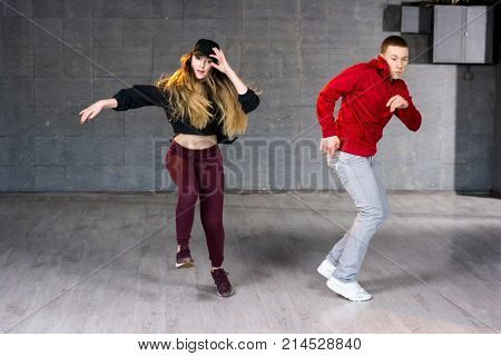 Hip-hop dancers in movement. Modern style dancers dancing contemporary dance on studio background. School of modern dance.