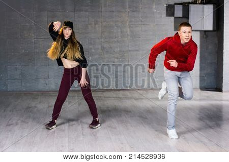 Couple of talented dancers performing hip-hop. Guy and girl dancing contemporary dance i studio. School of hip-hop culture.
