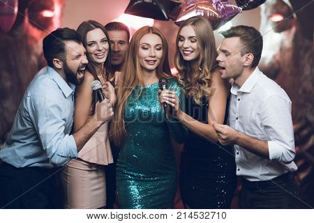 Young people in the club dance and sing. A man in a white shirt is holding a microphone and singing. His friends are singing along with him. They are in a trendy modern nightclub.
