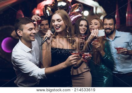 A woman in a black dress is singing songs with her friends at a karaoke club. Her friends do selfie. Her friends are singing along with her. Everyone is very cheerful and they smile.