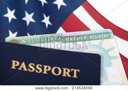 United States of America permanent resident card green card displayed with a US flag in the background and a passport in the foreground. Immigration concept. Close up with shallow depth of field.