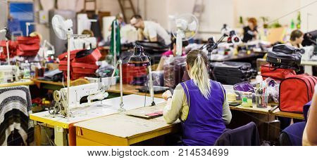 blonde woman in blue uniform manufacturing bags with sewing machine under the lamp. bags and air conditioners on the background. wide-screen photo