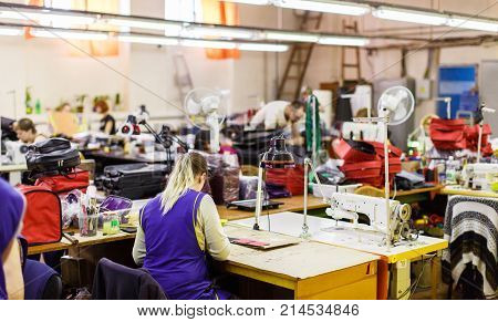 blonde woman in blue uniform manufacturing bags with sewing machine under the lamp. bags and air conditioners on the background.