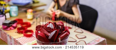 woman manufacturing heart-shaped red purses. purses are in focus. blurred background.