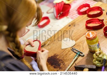 brown-haired woman manufacturing heart-shaped red purses on the wooden table. purse and hammer are in focus.