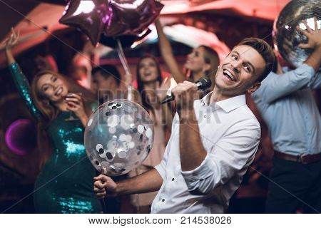 Young people have fun in a nightclub and sing in karaoke. On the foreground is a man in a white shirt and with a balloon in his hand. She sings and her friends are dancing.