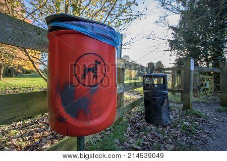 Dog poo waste litter bin. Trash can by UK public park entrance. Poop bag disposal. Cleaning up after pet dog walk.