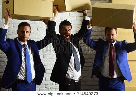 Leaders hold big carton boxes above heads on brick wall background. Businessmen wear smart suits and ties. Men with beard and smiling faces enjoy getting new job. Business and hard work concept.