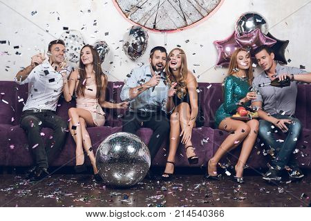 Young people rest in pairs in a nightclub. They drink champagne and sing songs. They are sitting on a large lilac sofa. Around them scattered confetti