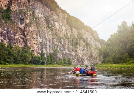 Group of tourists having leisure rafting on inflatable catamaran by river along a rocky shore.