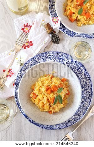 Two plate of pumpkin risotto and glass of wine white. Top view