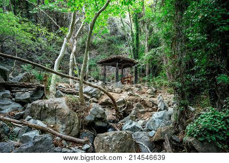 A small shed with a bench in the middle of a hiking trek to Caledonia waterfall near Platres Cyprus