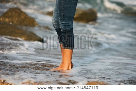 Woman barefoot walking on the beach between rocks. Close up leg of young woman walking along wave of sea water and rocks on the beach. Travel Concept.