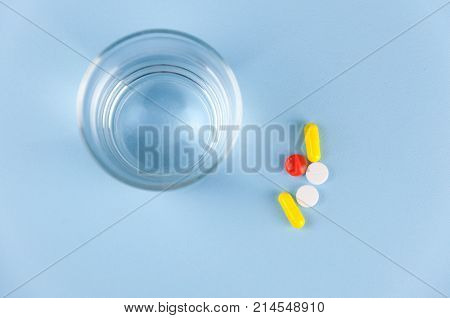 Several multicolored tablets with medicine lie on a lavish background, next is a glass with clear water