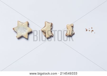 nibbled off cinnamon stars on white background as symbol of the advent season