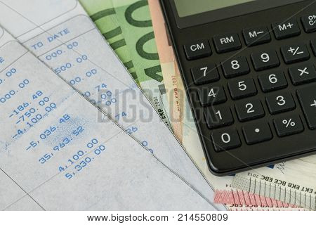 Financial office salary man or tax calculation concept as black calculator on pile of euro banknotes with numbers on carbon salary slips.
