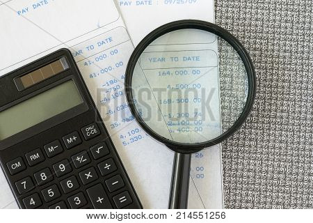 Financial office salary man or tax calculation concept as black calculator and magnifying glass with numbers on carbon salary slips.