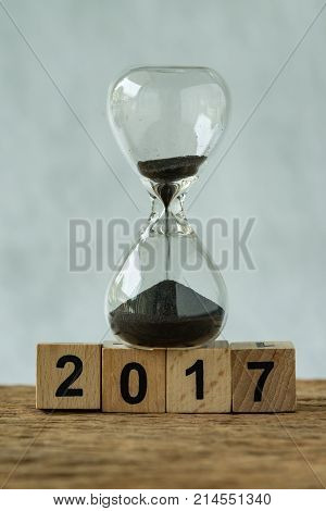 Year end 2017 business time countdown or improvement review concept as hourglass or sandglass with wooden cube block number 2017.