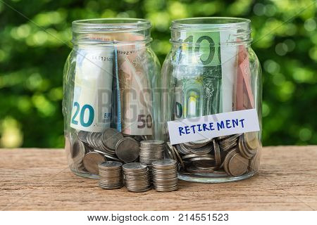 glass jar bottles labeled as retirement with full of coins and banknotes as savings or investing for retirement concept.