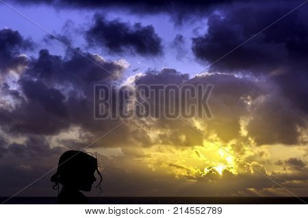 Silhouette of a young girl with sunrise over the ocean in background - Los Cocoteros, Lanzarote, Canary Islands, Spain