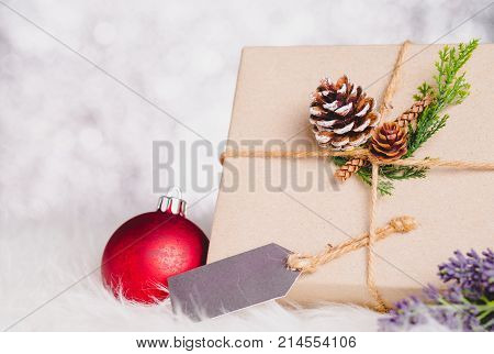 Brown Paper Craft Warped On Present Box With Label Tag Decorate With Pine Cone And Green Leaf Christ