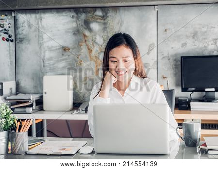 Asia businesswoman looking at laptop computer and smiling face and rest chin on hand with happy emotion from good news of business success in home office.