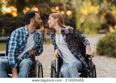 A couple of invalids on wheelchairs met in the park. They are drawn to each other for a kiss. They are in a beautiful green park.