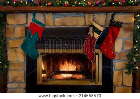 Three Christmas stockings hanging over a fireplace.