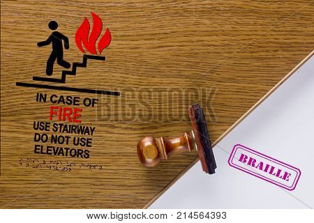 Poster sign with braille. Symbol in case of fire use stair way do not use elevator