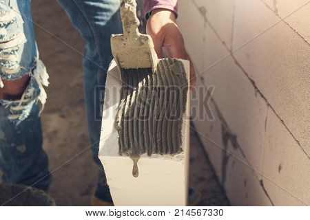 Construction Concept, Bricklayer Worker Installing Wite Blocks To Build Wall At Construction Site
