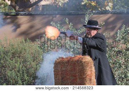 Participant Dressed In Period Cowboy Costume, Portraying  Gunfighter Shooting During