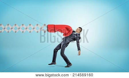 A businessman in side view gets hit with a large red boxing glove attached to a metal scissor arm on a blue background. Business and risk. Strong hit from life. Work competition.