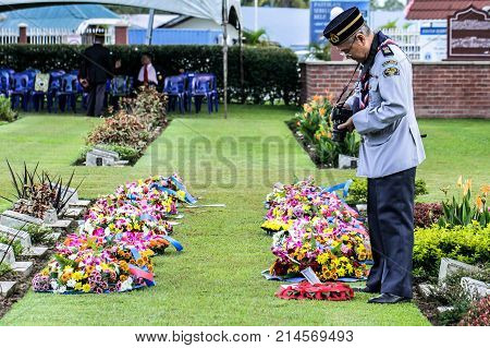 Labuan,Malaysia-Nov 12,2017:Malaysian's leader scout uniform eader taking photo with DSLR camera during the Remembrance Day at Labuan War Memorial park in Labuan,Malaysia.