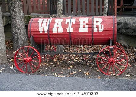 Old red water trailer with spoke wheels