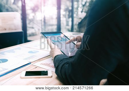 Rear View Of Businessman Pointing To Graph And Summary Report On Digital Tablet Screen With Analysis