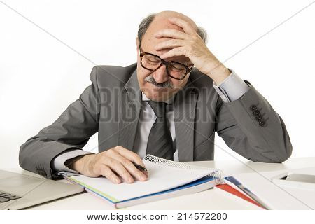 senior mature business man with bald head on his 60s working stressed and frustrated at office computer laptop desk writing on notepad overwhelmed in job problems concept suffering headache