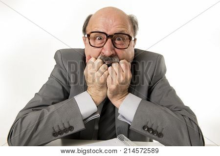 60s bald senior office boss man furious and angry gesturing upset and mad sitting on desk with paperwork in business and job problems and stress concept isolated on white background