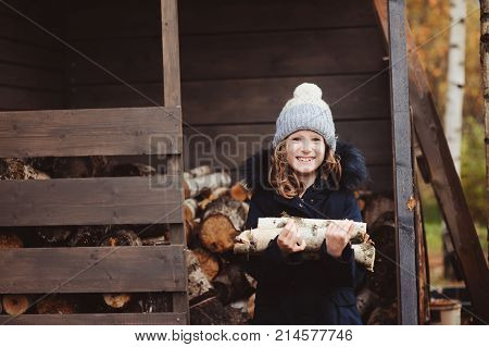 happy child girl picking firewood from shed in winter or autumn