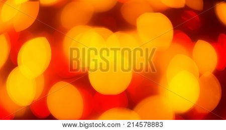 Red and yellow color light blurred background, unfocused. Christmas or other holiday decorations, garland illumination bokeh, top view