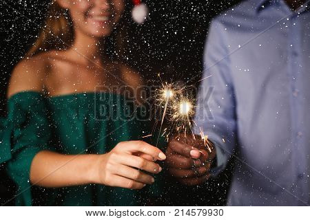 Holiday background with sparklers. Cropped shot of young friends holding bengal lights, closeup, selective focus. Birthday or winter holidays celebration, greeting card mockup