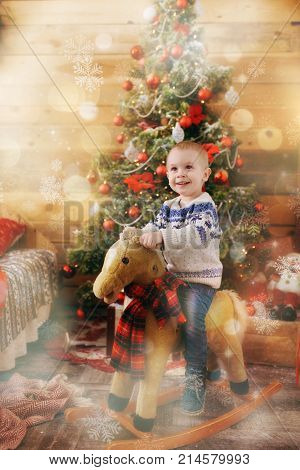Happy Cute Little Baby Boy On Rocking Horse At Christmas Tree With A Toy In Decorated New Year Room