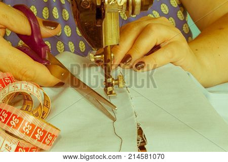 Woman hand on sewing machine.Dressmaker work on the sewing machine. Hobby sewing fabric as a small business concept. sewing machine and female scissors poster