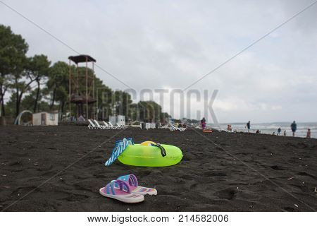 Ball swimming glasses sandal and Floating Ring on beach. Beach life tourists at the beach of the image desired blur overcast. In the summer vacation