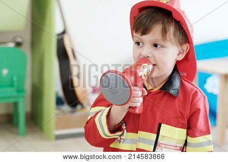 Boy playing as fireman police occupation in kindergarten class kid occupation education concept