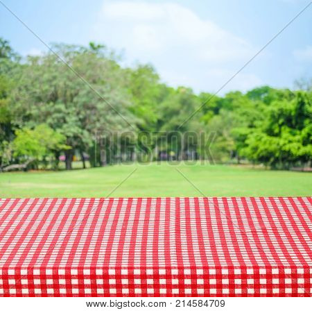 Empty table with red tablecloth over blur garden and bokeh background for food and product display montage